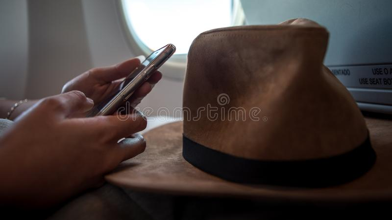 Asian woman passenger using device phone during flight interior airplane royalty free stock photography