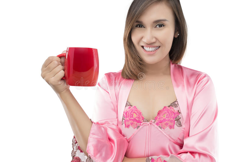 Asian woman in pink satin nightwear holding coffee red cup stock image