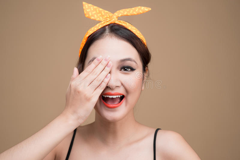 Asian woman with pinup makeup cover eyes by hands. stock photography