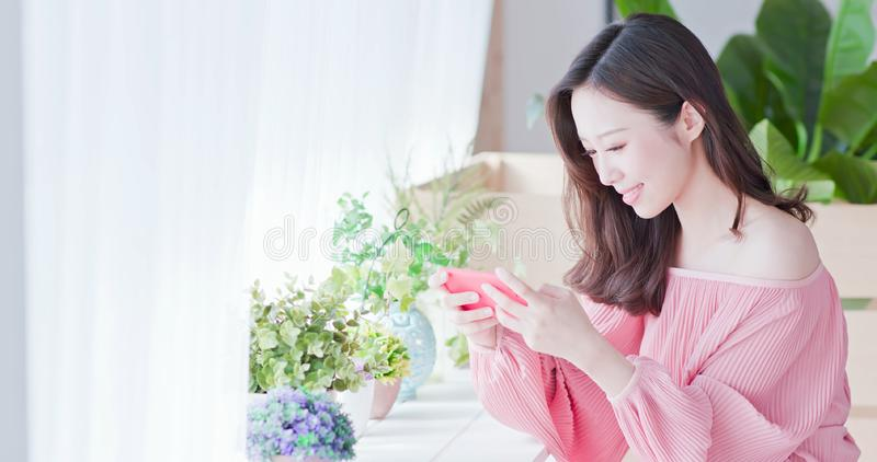 Asian woman play mobile game. By smart phone stock photo