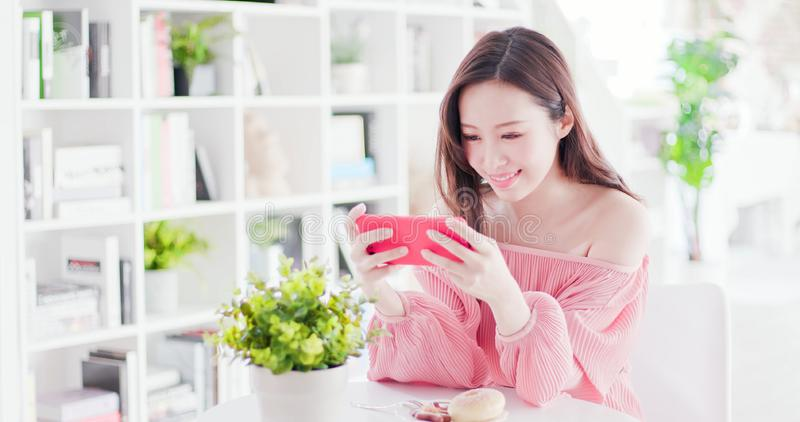 Asian woman play mobile game. By smart phone in a restaurant royalty free stock images