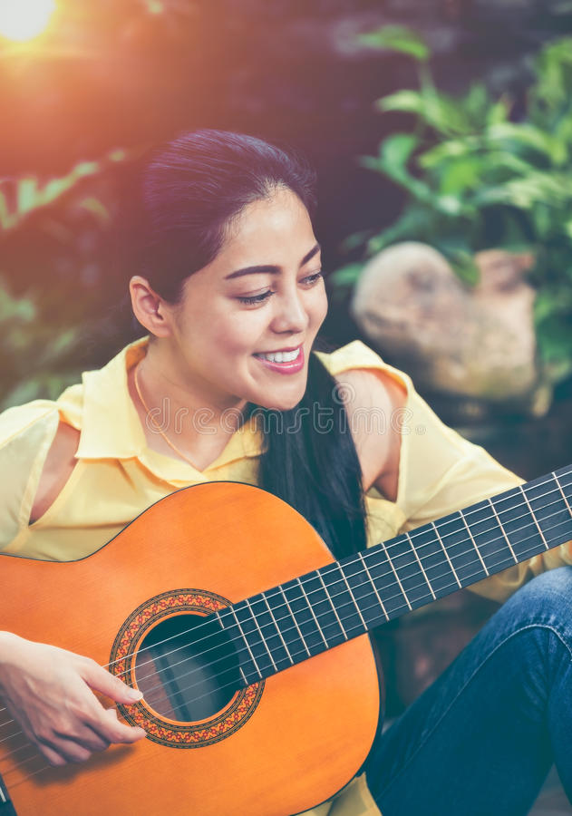 Asian woman playing acoustic guitar with bright sunlight. Vinta royalty free stock image