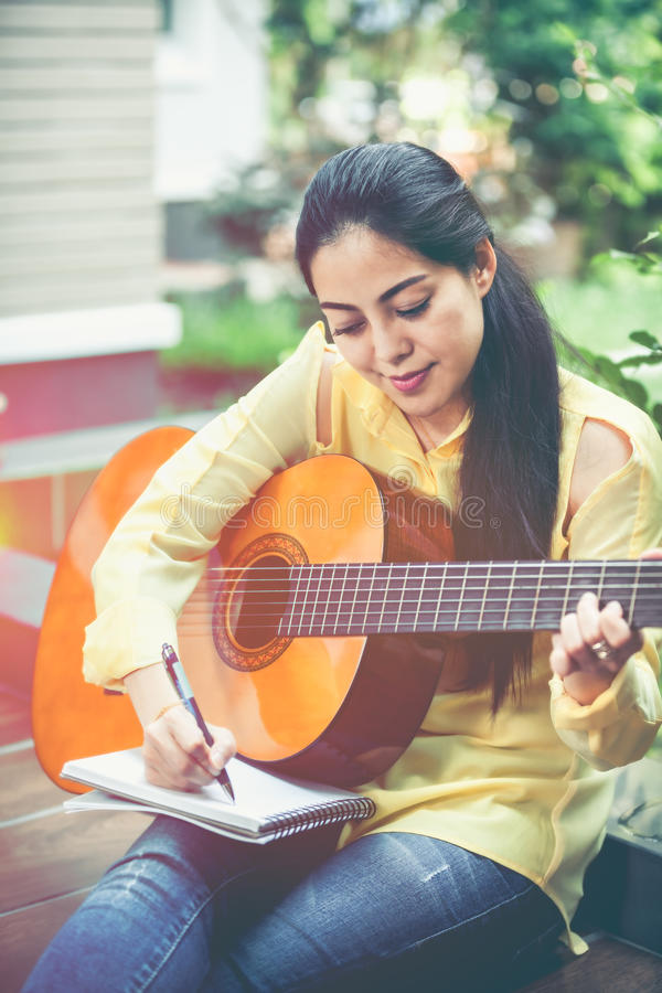 Asian woman playing acoustic guitar with bright sunlight. Vinta stock images