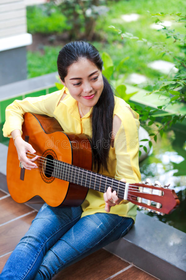 Asian woman playing classic guitar, outdoor at daytime with brig. Pretty musician smiling and having fun enjoy hobby concept. Asian woman playing classic guitar royalty free stock images