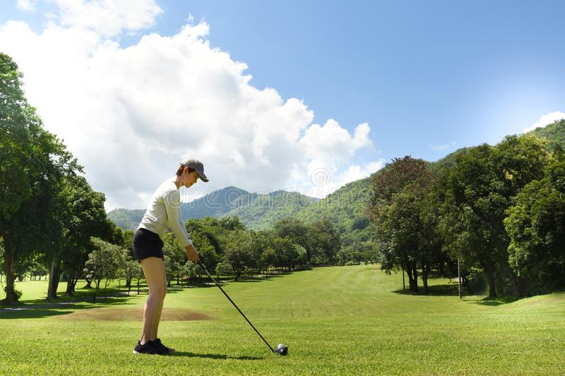 Asian woman playing golf on a beautiful natural golf course stock photo