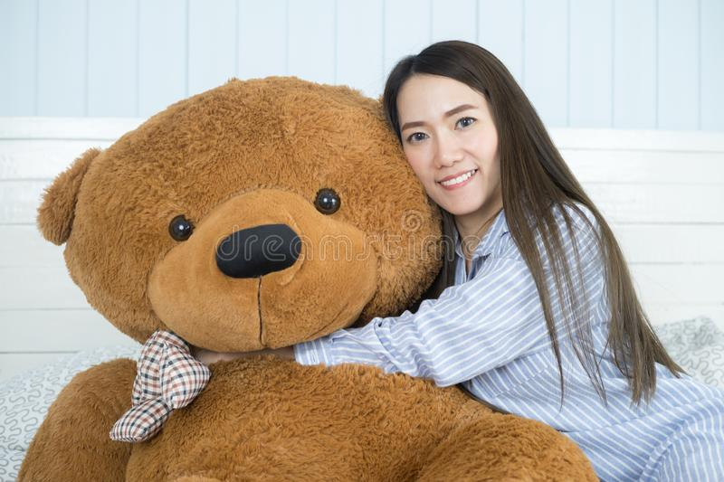 Asian woman playing with teddy bear in the bedroom. Asian woman playing with teddy bear on the bed in her bedroom royalty free stock photos