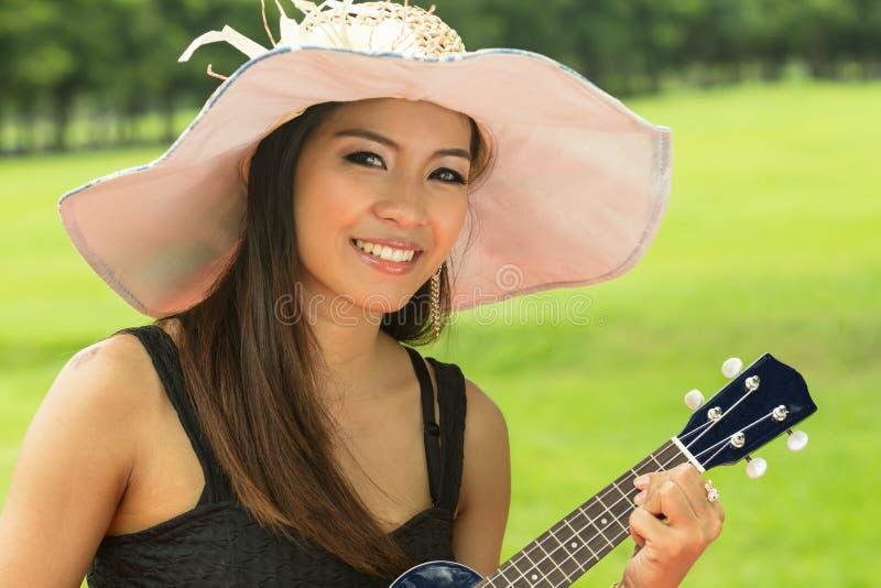 Asian woman playing ukulele stock photos