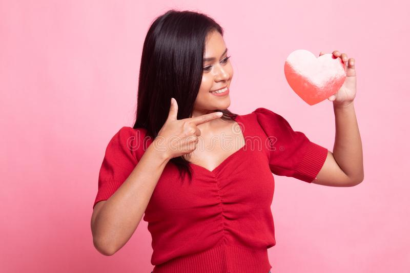 Asian woman point to red heart. On pink background stock photos