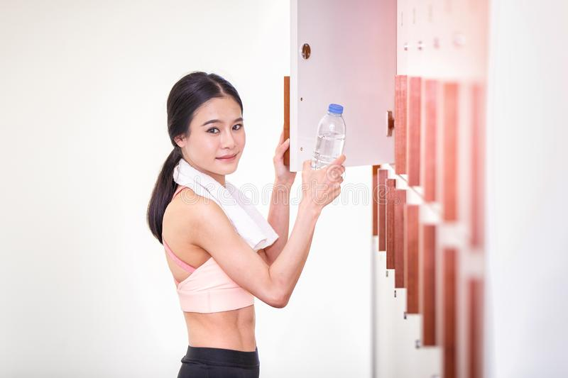 Asian woman pose and smiling putting water bottle in locker room of sports center and row of wood locker in the room royalty free stock image