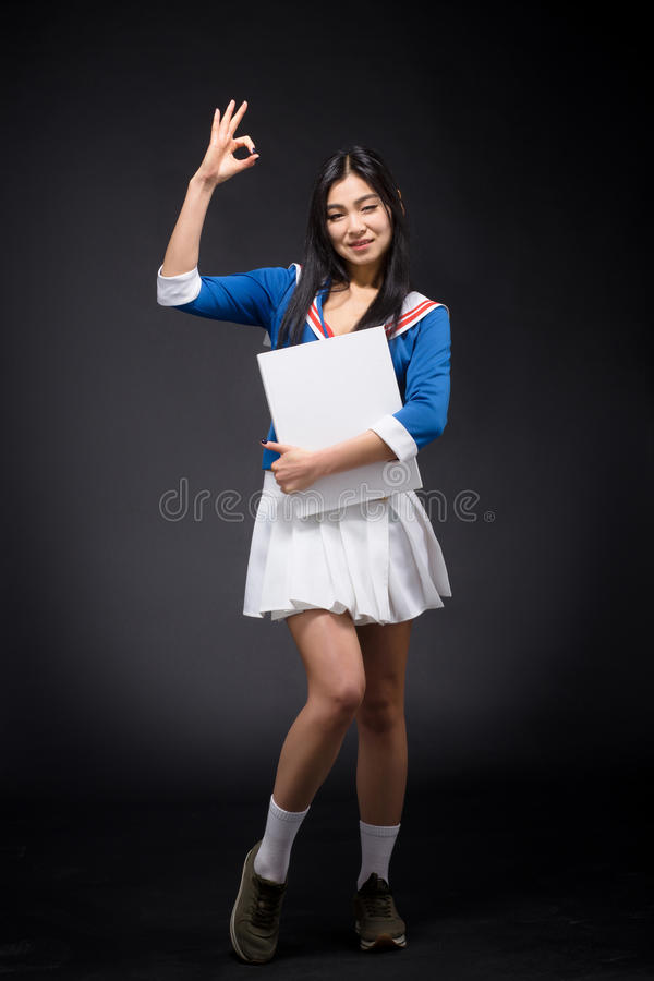 Asian woman posing with blank poster in studio. Pretty lady showing okay sign and smiling for camera isolated on grey background. Asian woman with red lips stock photography