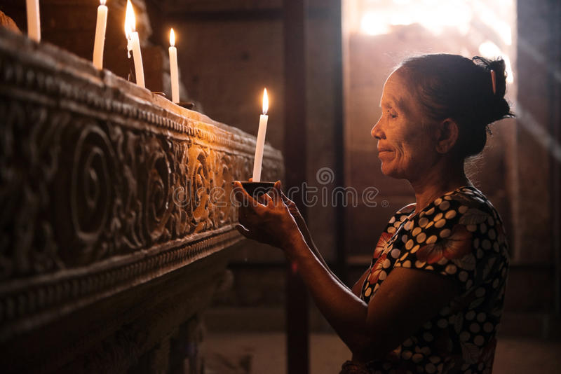 Asian woman praying with candle light royalty free stock photo