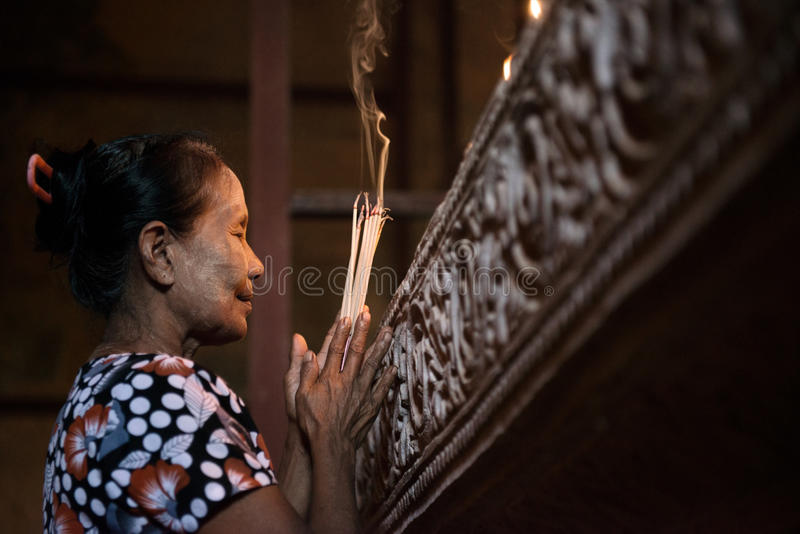 Asian woman praying with incense sticks royalty free stock photo