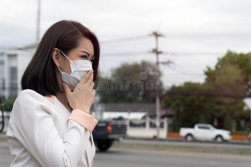 Asian woman in protective mask feeling bad on the street in the city with air pollution., Black short hair suffer from sick and we stock photo