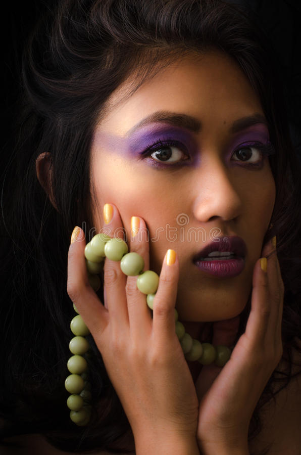 Asian woman with purple make-up and green necklace. Asian woman with purple make-up with black background holding green necklace with gold fingernails stock images