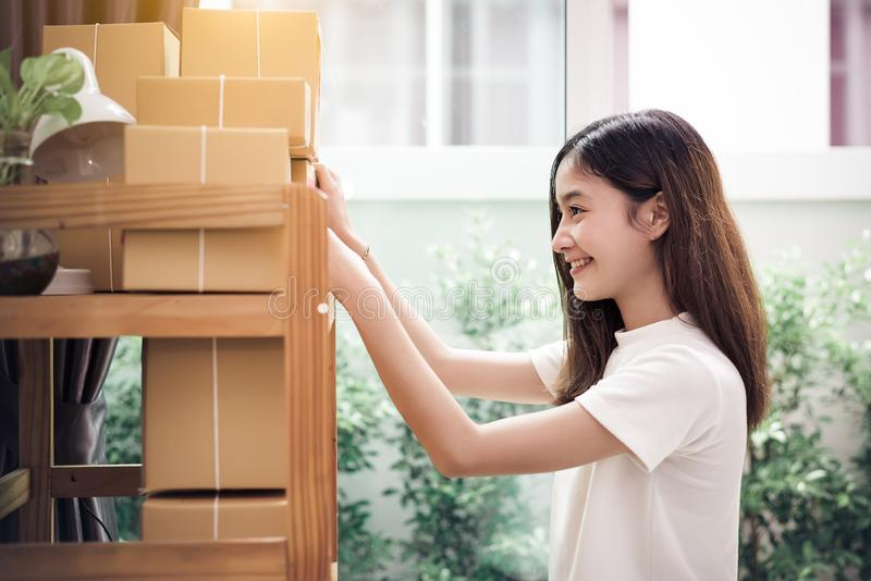 Asian woman put sticky memo paper note on parcel mail box and ready to send to customer. Business owner and Online shopping stock image