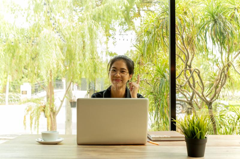 Asian woman puts finger up thinking of idea with laptop in coffee shop. royalty free stock photos