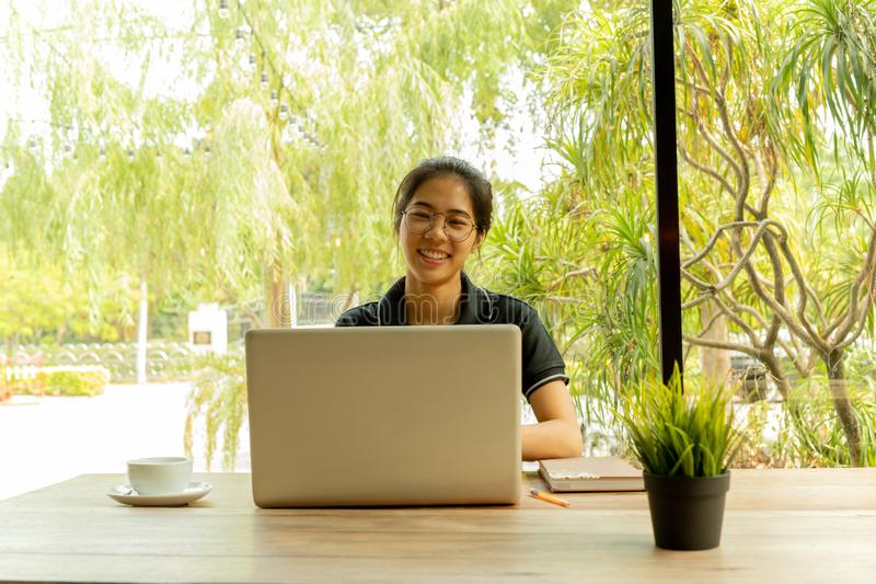 Asian woman puts finger up thinking of idea with laptop in coffee shop. stock image