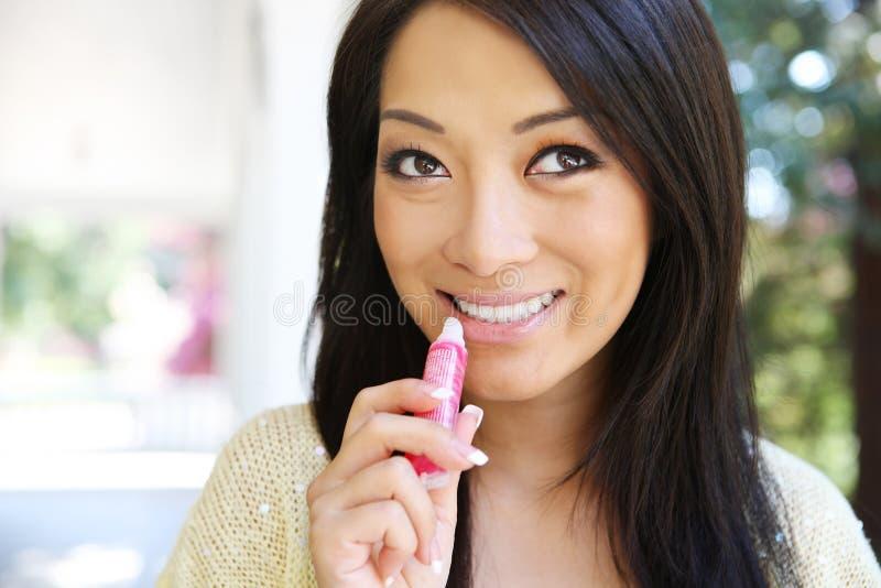 Asian Woman Putting on Lip Gloss