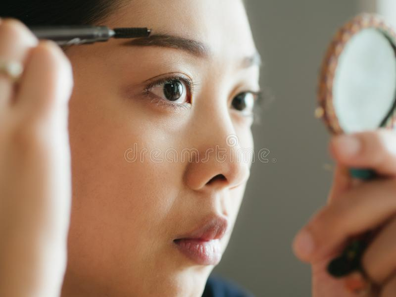 Woman is putting make up on her eyebrows with the eyebrows pencil. stock photography