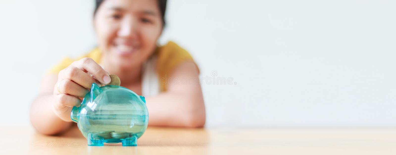 Asian woman putting money coin in to clear piggy bank metaphor s royalty free stock image