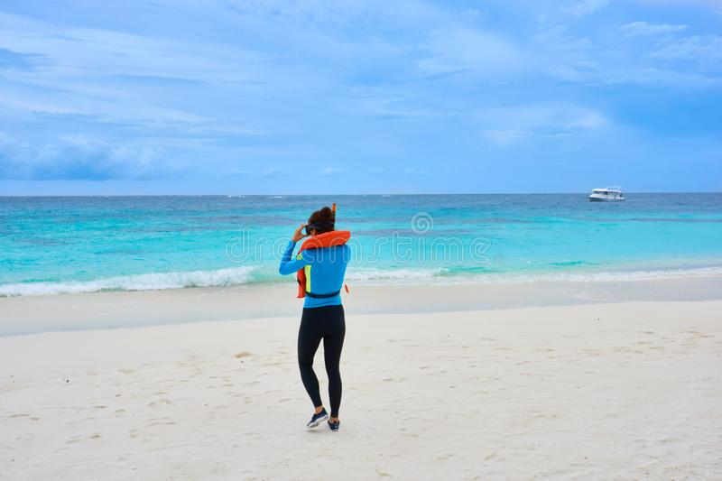 Asian woman in rash guard at the Coco Bodu Hithi resort beach walking towards turquoise sea for snorkeling. royalty free stock photo