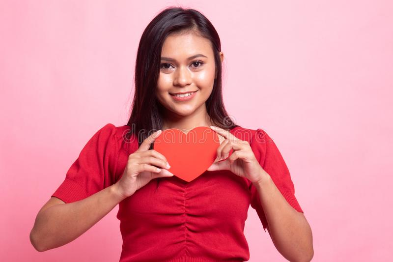 Asian woman with red heart. On pink background stock photography