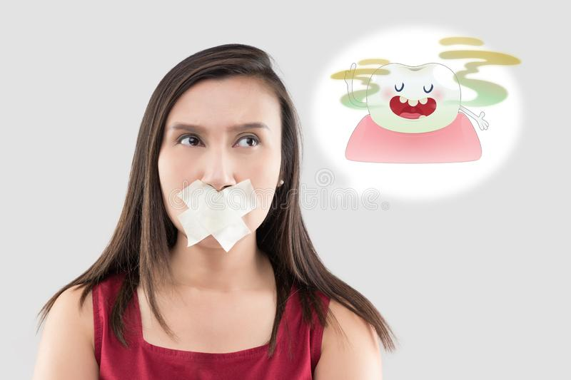 Bad breath or Halitosis. Asian woman in the red shirt holding a brown paper with the yellow teeth cartoon picture of his mouth against the gray background, Bad stock images