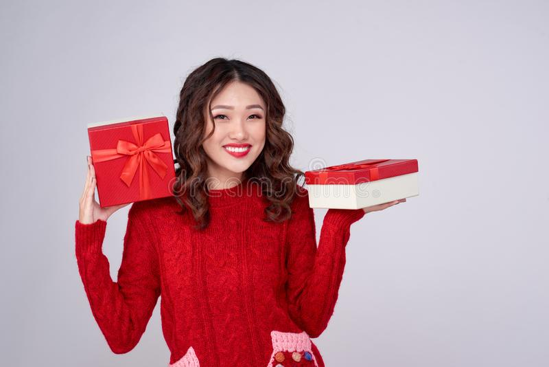 Asian woman in red warm clothes with gifts. Holidays New Year and Christmas stock photography