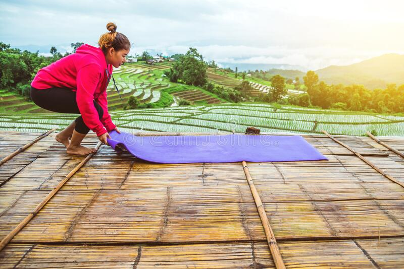 Asian woman relax in the holiday. Play if yoga. On the balcony landscape Natural Field.papongpieng in Thailand stock image