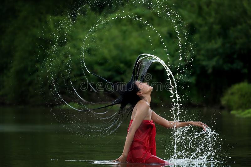 Asian woman relaxing and enjoying playing with water and splash at tropical exotic river with turquoise amazing color water in bea. Utiful destination forest stock photography