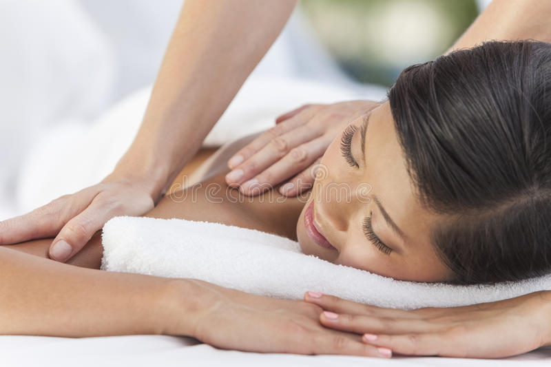 Asian Woman Relaxing At Health Spa Having Massage. An Asian Chinese women relaxing outside at a health spa while having a massage treatment stock image