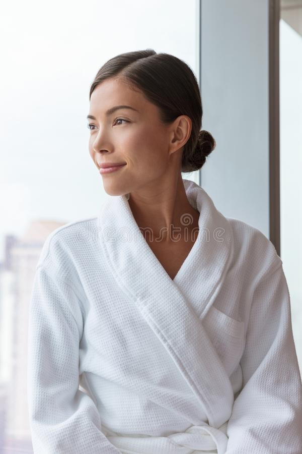 Asian woman relaxing at luxury hotel spa wearing bathrobe looking at window portrait. Pampering comfort lifestyle at resort. Or at home royalty free stock photos