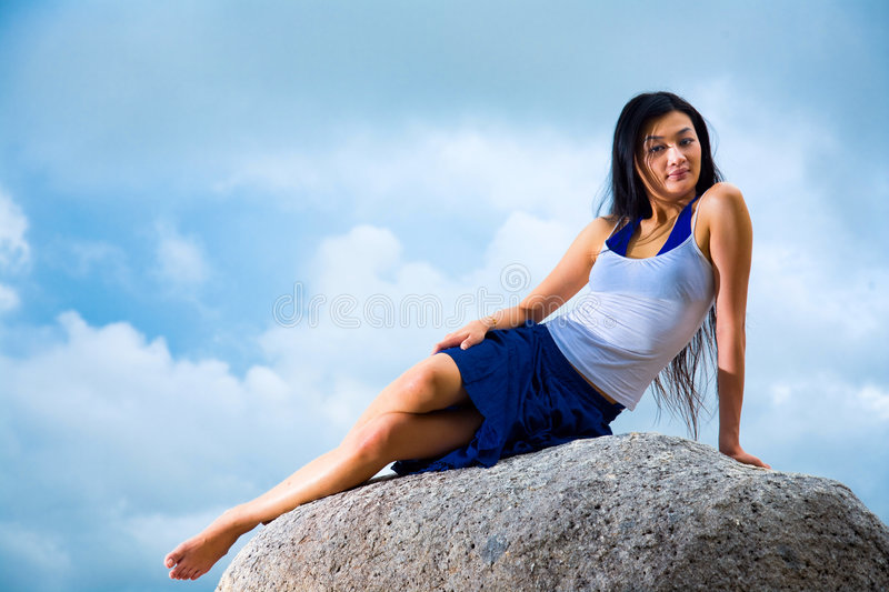 Asian Woman Relaxing On The Rock Royalty Free Stock Photo