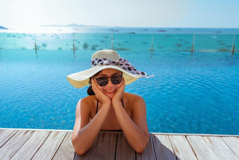 Asian woman relaxing in swimming pool with sunbathe royalty free stock photo