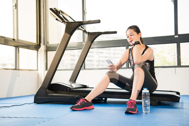 Asian woman rest sitting treadmill use smartphone and smartwatch. Asian woman rest sitting on treadmill use smartphone and smartwatch. indoors gym background stock photography