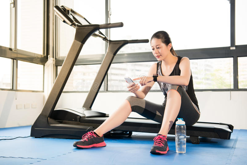 Asian woman rest sitting treadmill use smartphone and smartwatch. Asian woman rest sitting on treadmill use smartphone and smartwatch. indoors gym background royalty free stock image