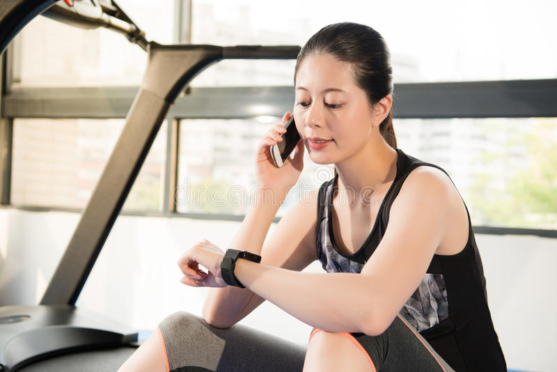 Asian woman rest on treadmill use smartphone and smartwatch. Asian woman rest sitting on treadmill use smartphone and smartwatch. indoors gym background. health stock photo