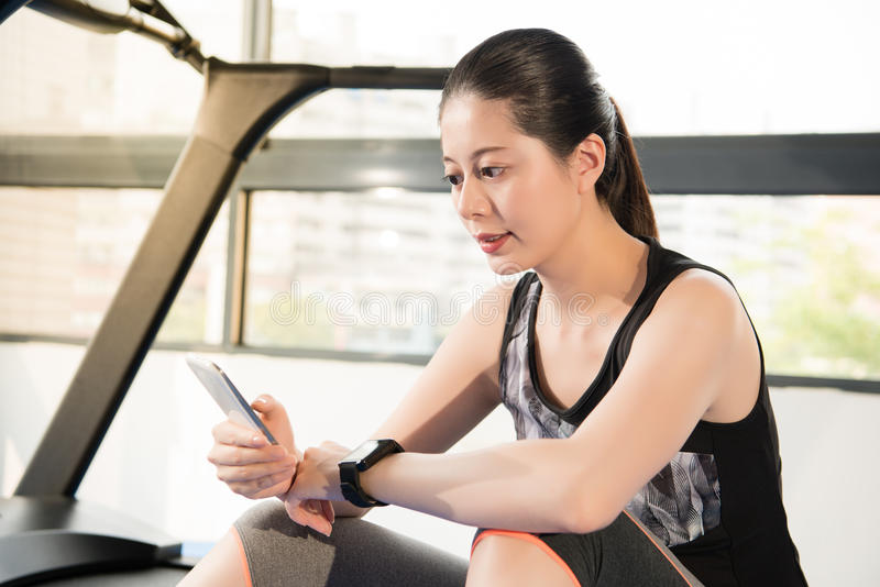 Asian woman rest on treadmill use smartphone and smartwatch. Asian woman rest sitting on treadmill use smartphone and smartwatch. indoors gym background. health stock image