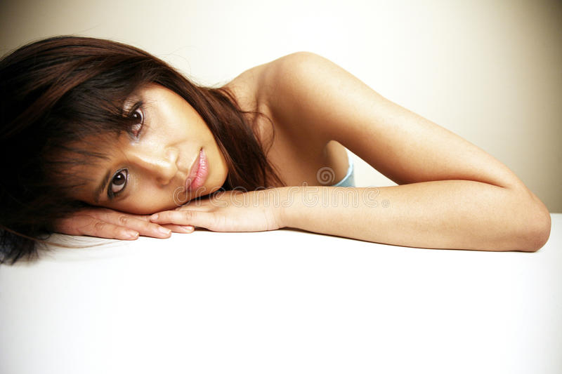 Asian woman resting. Her head on her hands royalty free stock photography
