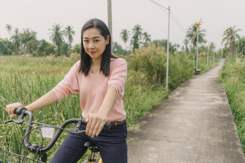 Asian woman ride bicycle on the local street with greenery view stock image