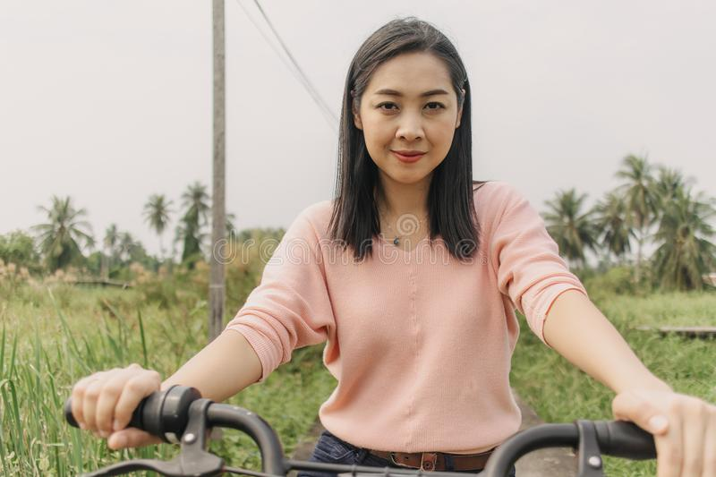 Asian woman ride bicycle on the local street with greenery view royalty free stock photography