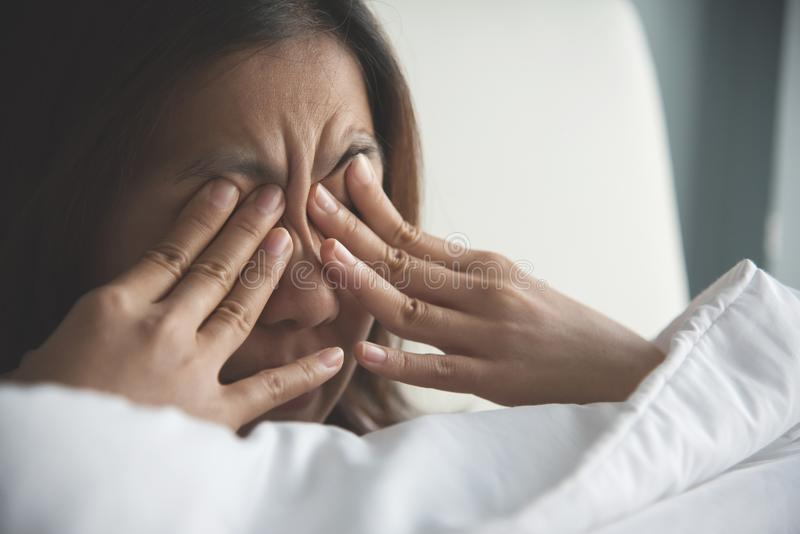 Asian woman rubbing eyes with her hands on her bed. Copy space royalty free stock images