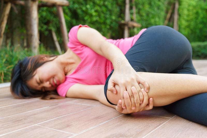 Asian woman runner laying on the floor and touching her injured stock images
