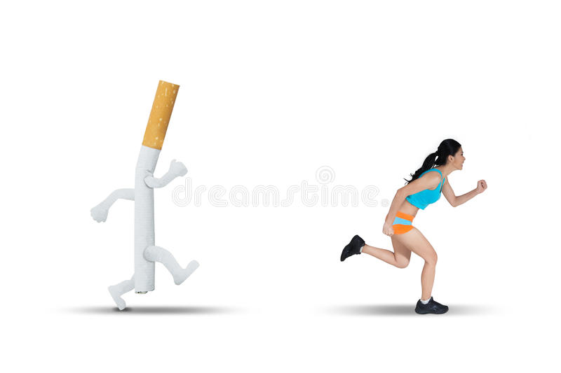 Asian woman running away from a cigarette. Image of Asian woman wearing sportswear while running away from a cigarette in the studio stock photos