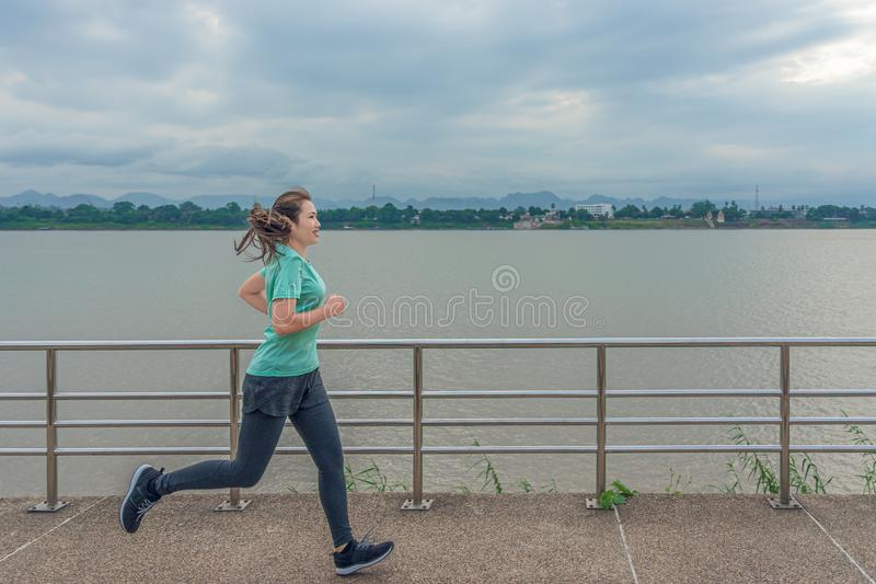 Asian woman running on the street with a view of the river in the morning royalty free stock photos