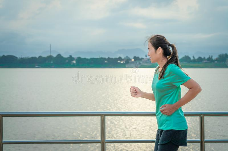 Asian woman running on the street with a view of the river in the morning royalty free stock images