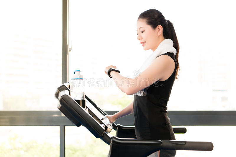 Asian woman running treadmill use smartwatch check pulse rate. Beautiful asian woman running treadmill use smartwatch check pulse rate. indoors gym background royalty free stock photo