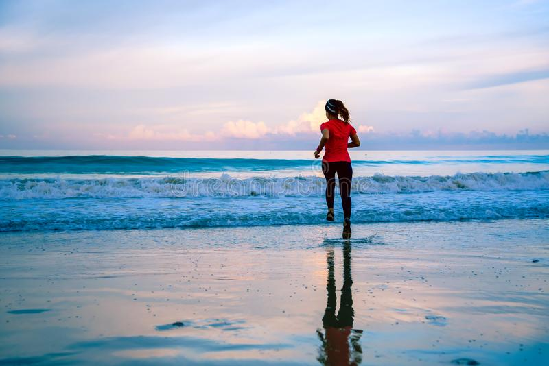 Girl running workout jogging on the beach in the morning. relax and happy with running on the sea. in summer. Asian woman the running workout in the morning royalty free stock photo