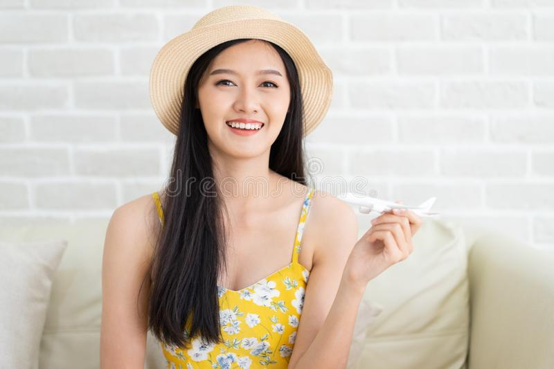 Asian woman`s hand flying toy plane .Beautiful young woman smiling planning vacation summer trip.she think and sitting sofa on royalty free stock images