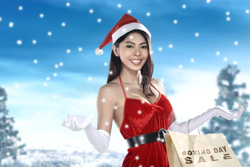Asian woman in Santa costume holding shopping bag with Boxing Day Sale text stock photography